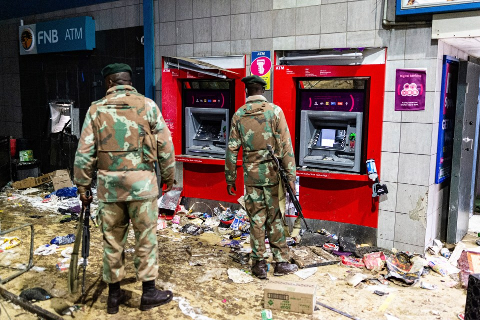 Soldiers, seen here guarding cash machines, have been deployed in KwaZulu-Natal and Gauteng provinces to deal with violent protests