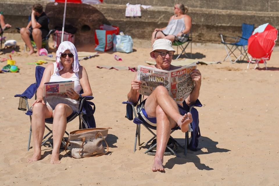 A couple enjoy Britain's best newspaper on the beach in Bridlington, Yorkshire
