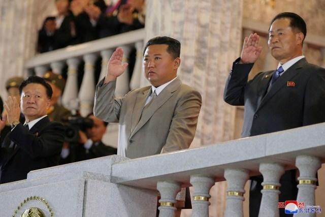 Kim greeting crowds at a bizarre midnight parade marking North Korea's 73rd anniversary