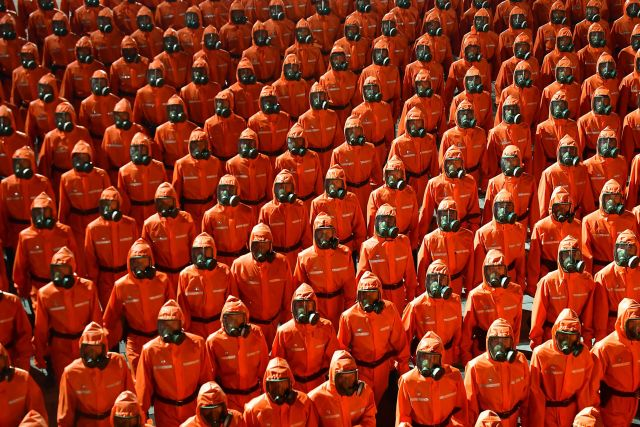 Men kitted up in red hazmat suits and gas masks took part in the bizarre midnight parade