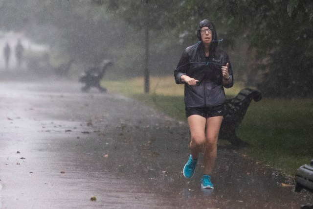 A woman jogged during heavy rain in Greenwich Park, South East London yesterday