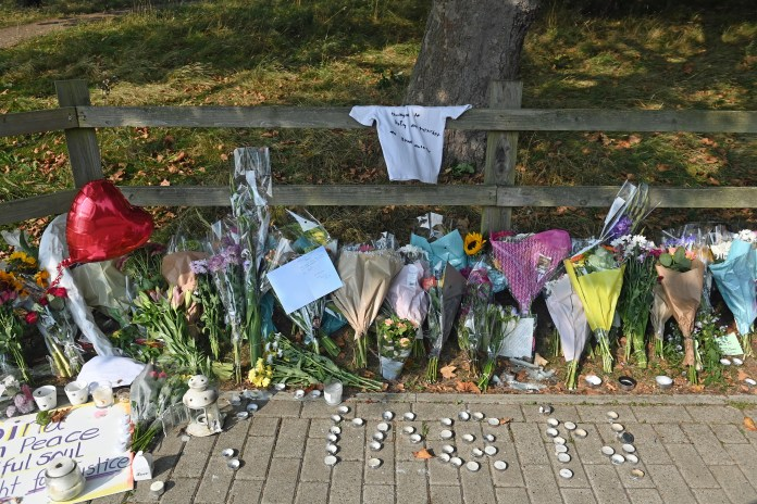 Mourners leave flowers, candles and condolence messages at the scene