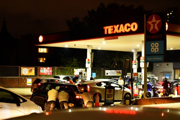 Helpers were seen pushing a car that ran out of fuel in the courtyard of a petrol station in south London last night