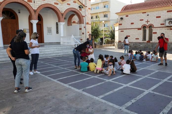 Local school children gather outside away from danger