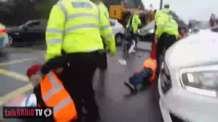 Footage recorded at the scene shows tired police officers pulling campaigners