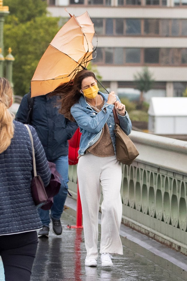 A woman struggles with her umbrella on Westminster Bridge this morning