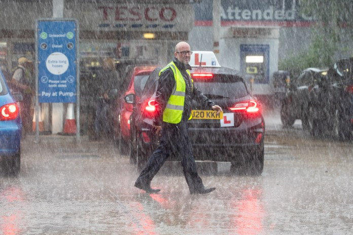Tesco workers trying to direct queues during a rain storm at a petrol station in Ely, Cambridgeshire