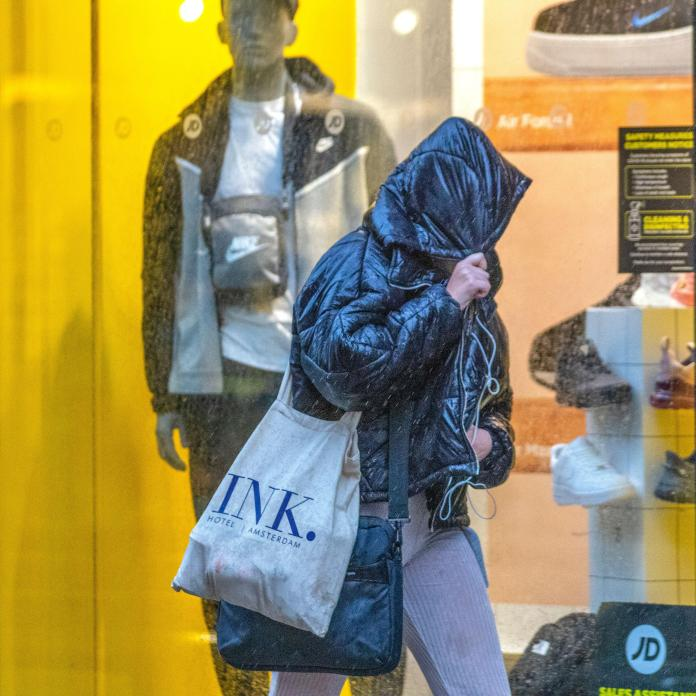 Shoppers in Preston, Lancashire, trying to keep themselves dry this morning