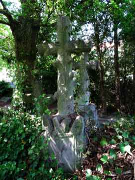 Headstone cross in dappled light