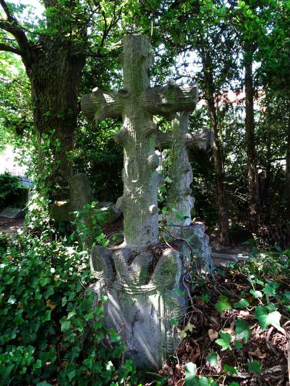 Headstone cross in dappled light