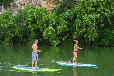 A man and woman paddling down a river on a Journey Epoxy SUP.