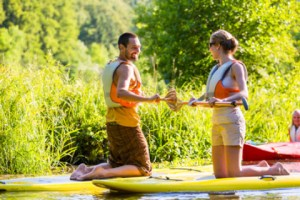 fully clothed man and woman stand up paddle boarding on a river