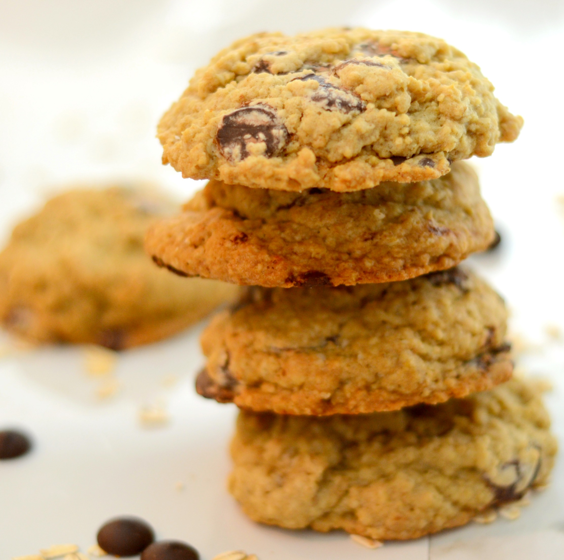 A stack of oatmeal chocolate chip cookies aganist a white background with a few chocolate chips and oats sprinkled in the foreground