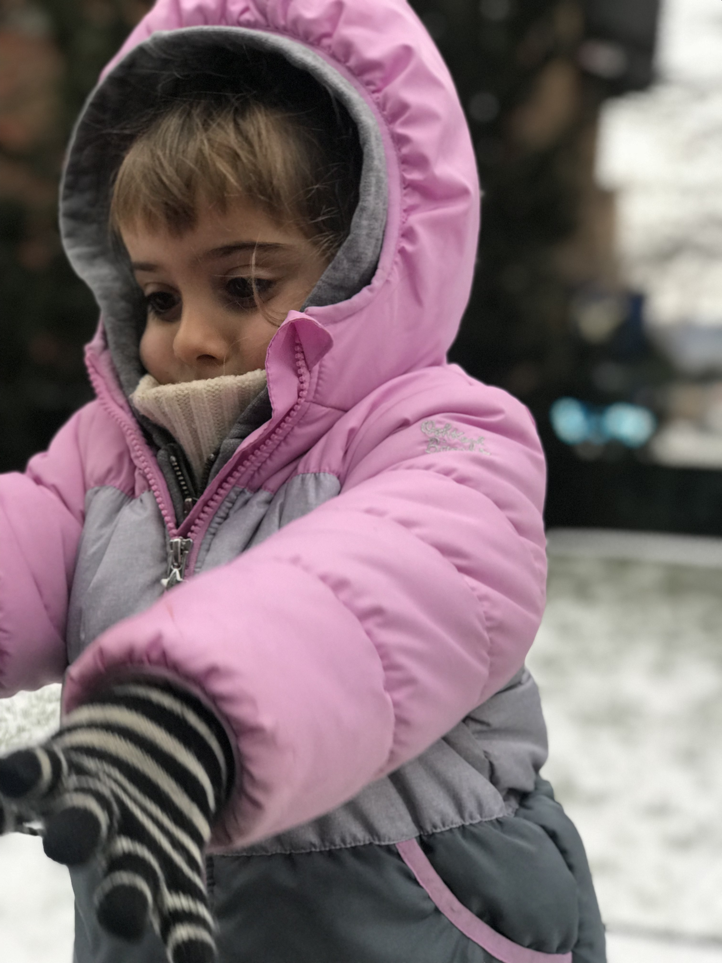 toddler bundled up in pink coat with snow in background, new york city highline park
