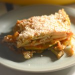 vegan gluten free lasagna on a plate with sunshine coming in from a nearby window