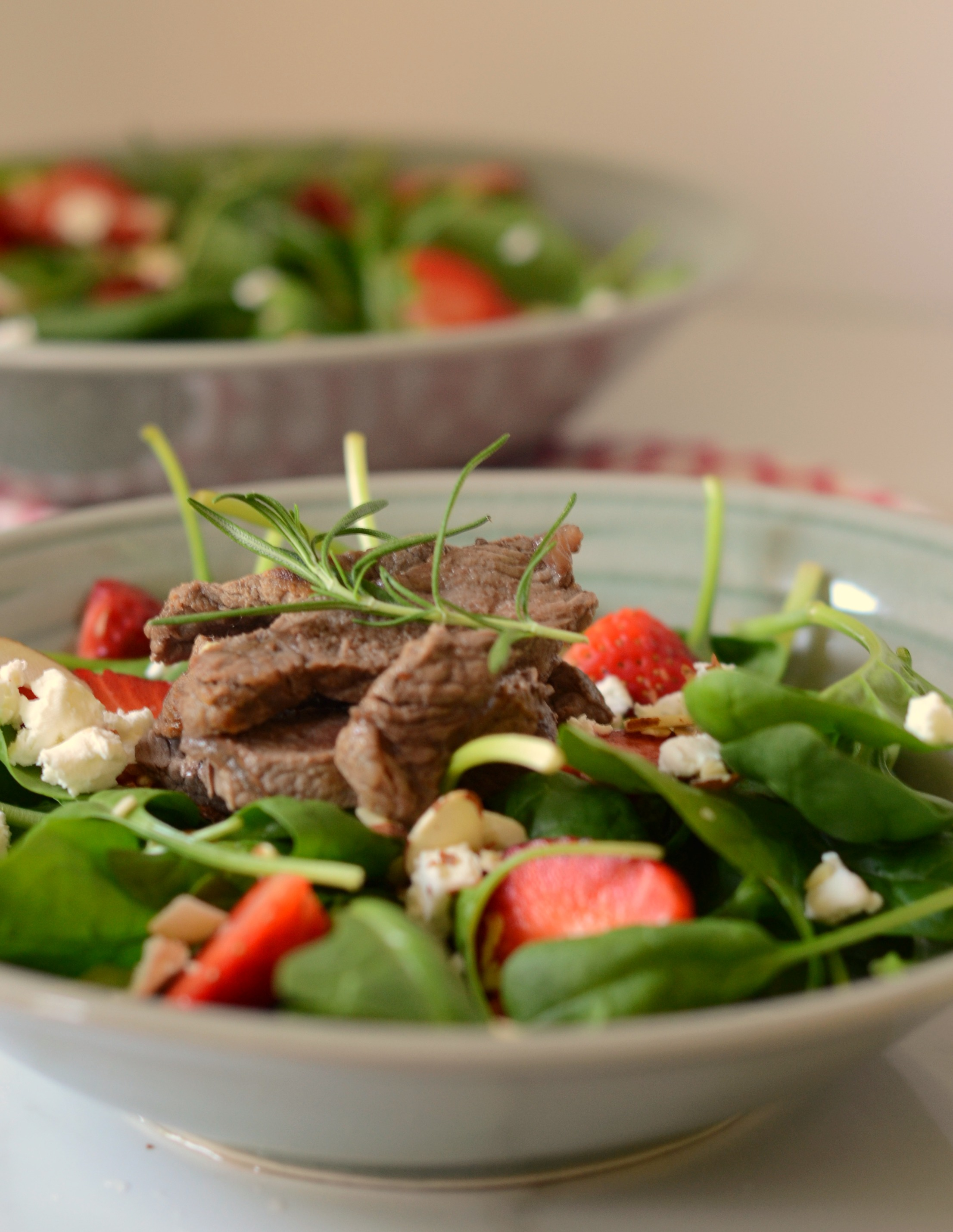 close up of a bowl of spinach and other greens topped with strawberries, steak and goat cheese