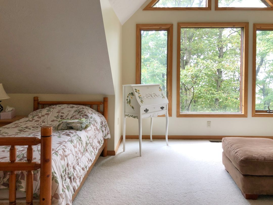 Twin bed near triangle windows in cabin loft