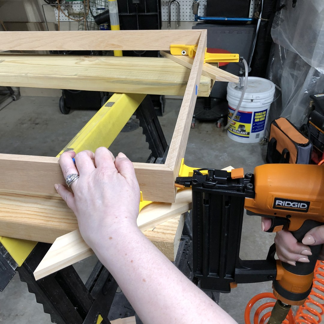 Using a nail gun to secure frame corners
