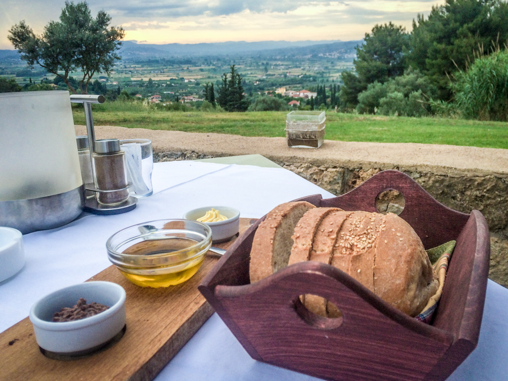 Enjoying my olive oil and olive spread with a view of olive trees at Hotel Europa, Ancient Olympia