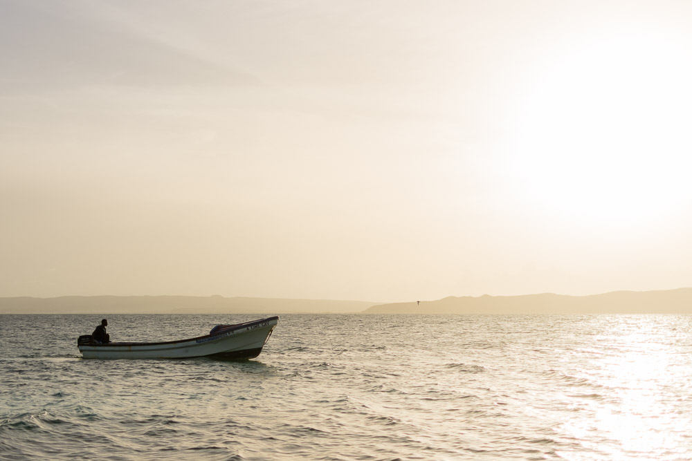 Boat returning for beach visitors at sunset