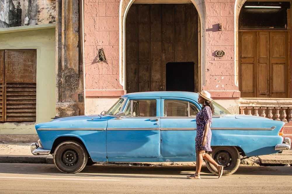 Toni-Ann walking beside a vintage cars in Havana Cuba