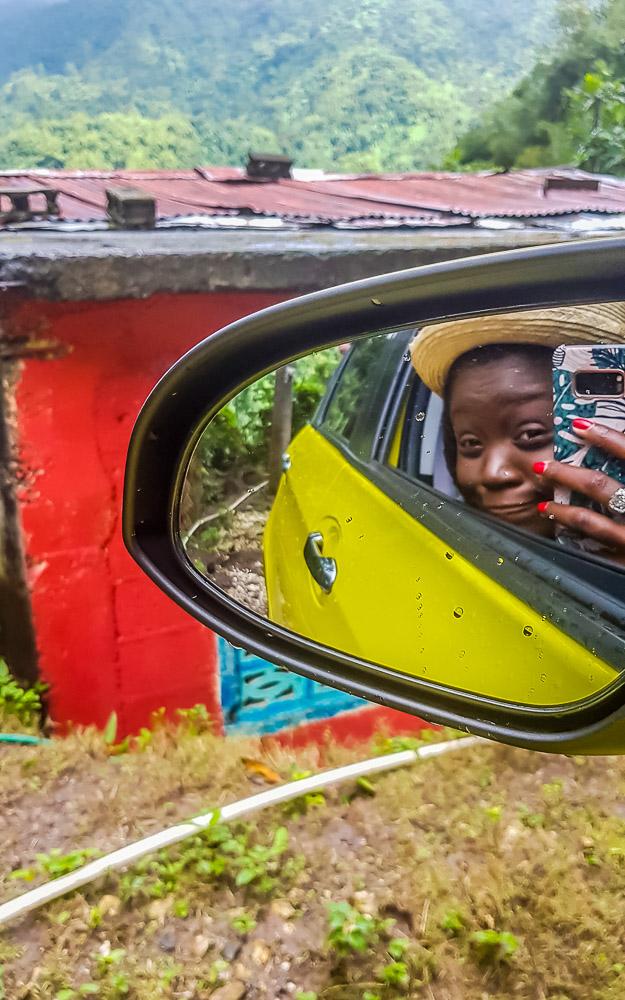 Girl taking a selfie in a car mirror