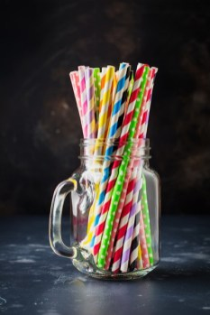 Multicolored paper rolls for cocktail or straws in glass jar on dark background. Selective focus.