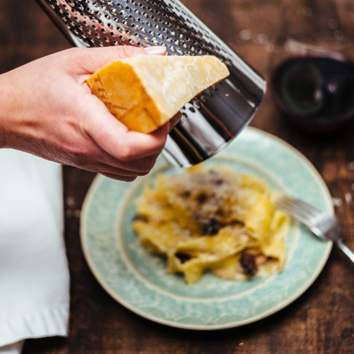 Toping the best mushroom pappardelle with grana padano cheese