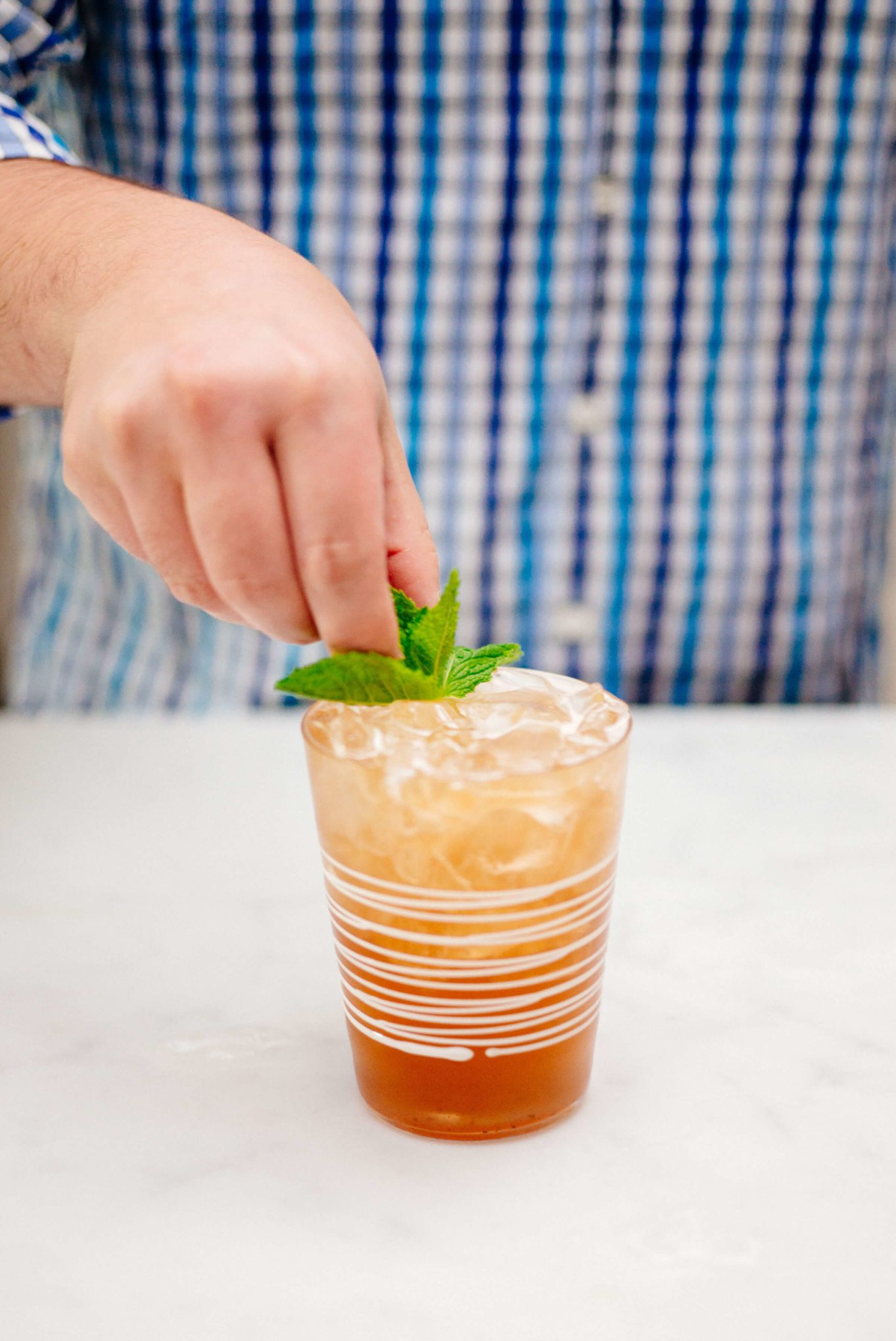 The Taste SF is garnishing a jack and ginger cocktail with pomegranate ginger ale with a sprig of mint