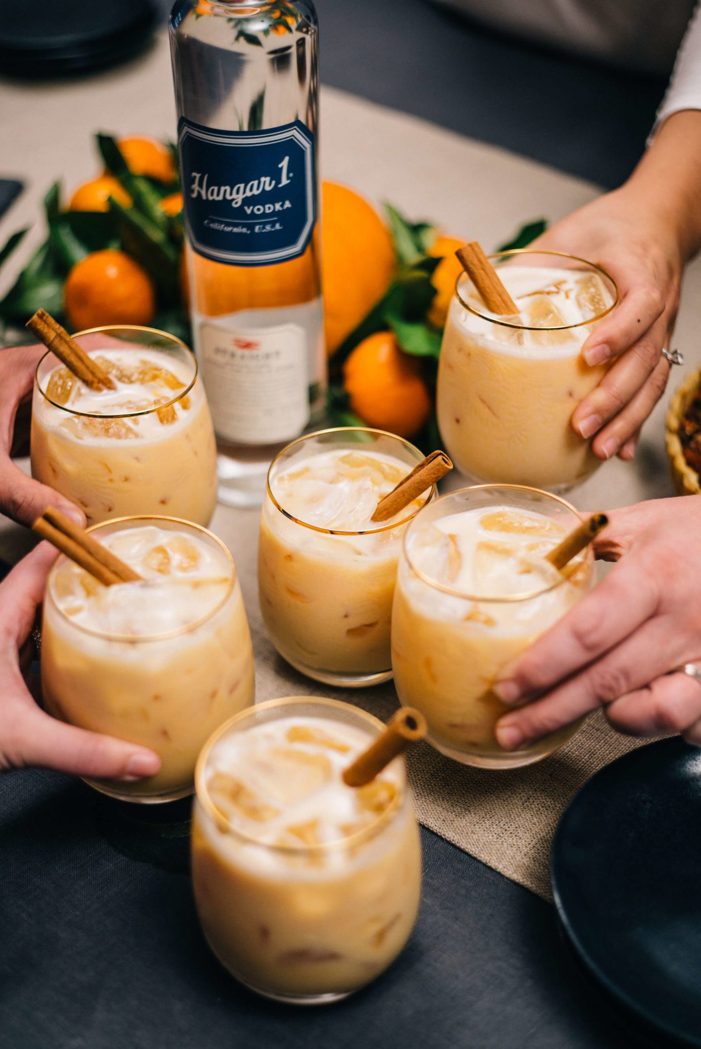 Glasses filled with Pumpkin Spice Cocktails, garnished with cinnamon sticks, and made with with Hangar 1 Vodka and horchata liquor made by The Taste SF