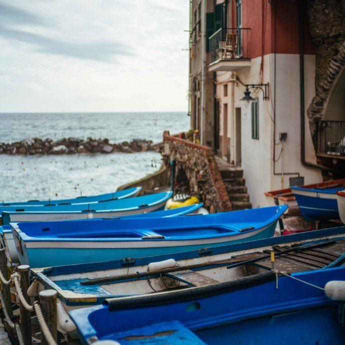 Scenes from riomaggiore in Cinque Terre with boats lined up for tourists to cruise the coast of the Mediterranean Sea.