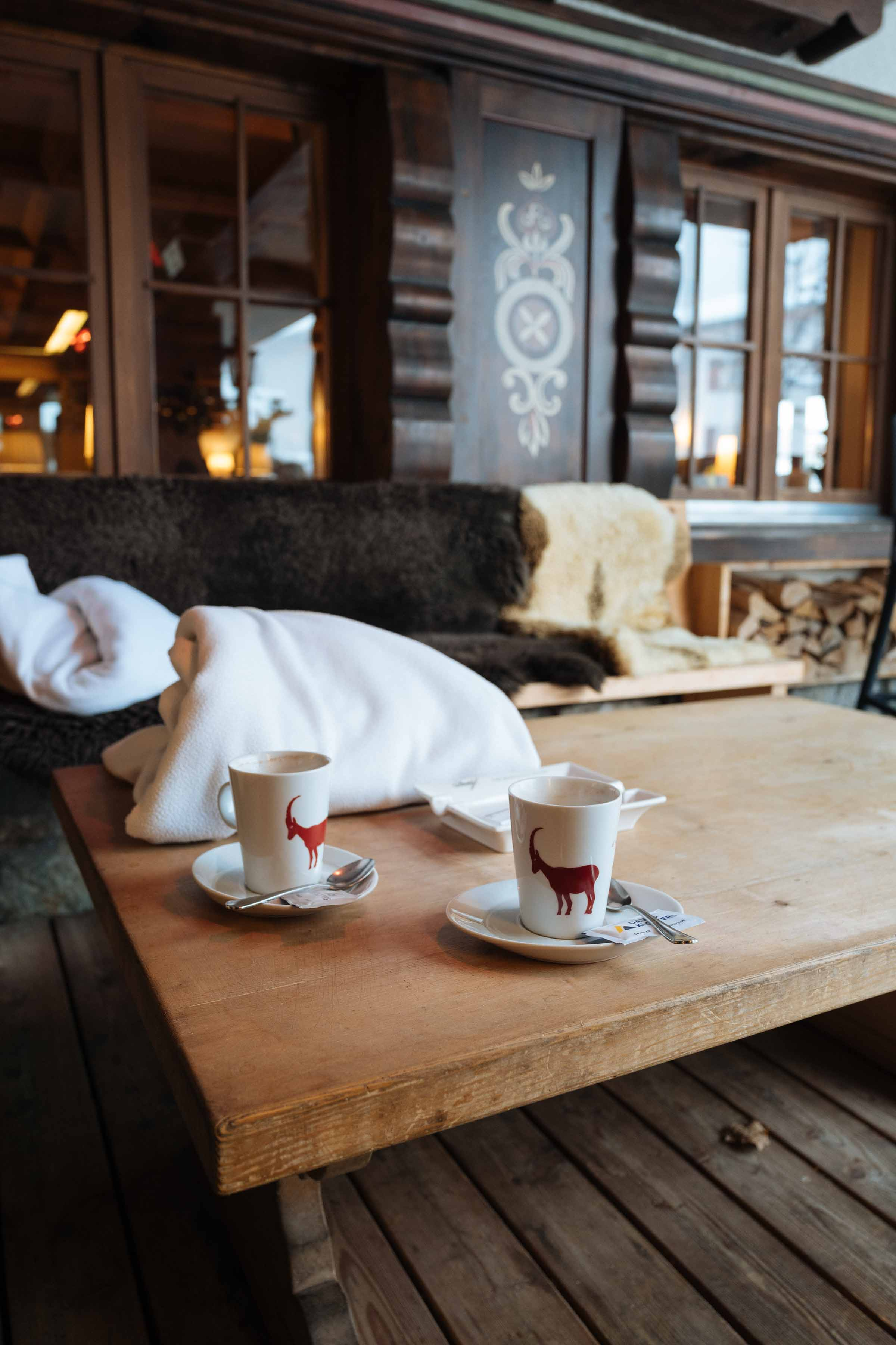 Travel to the alps in winter for a winter wonderland vacation! Cozy up with a blanket at one of these outdoor smoking lounges with heaters and sheep skins to stay warm. Order anything from the bar to enjoy or a hot chocolate while you watch the snow fall and the red Gotschnabahn cable car go up and down the mountain filled with skiers. | thetastesf.com #travel #switzerland #winter #drink