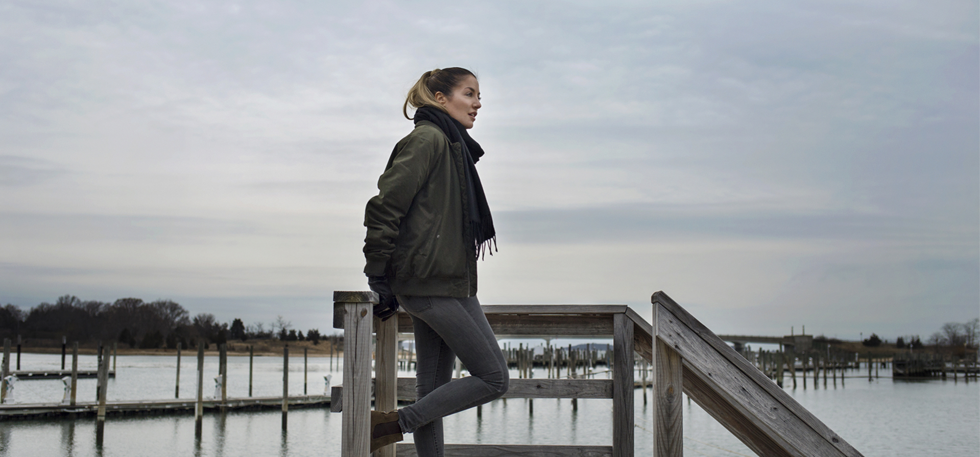 Taylor wearing an olive puffy jacket and standing on a dock in winter