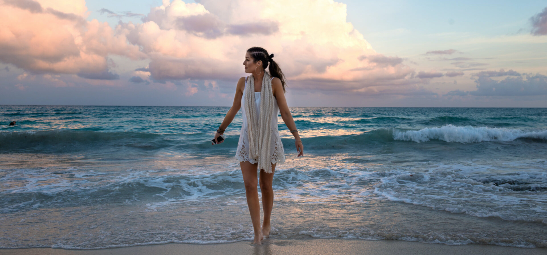 Taylor in a white dress standing in front of the sea, with a pink sunset in the background