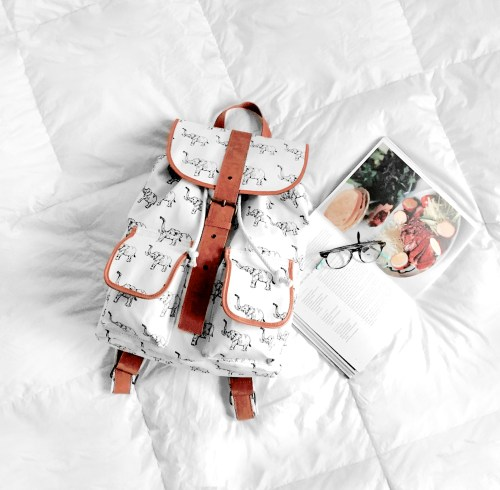 white backpack, cooking book and glasses on white duvet