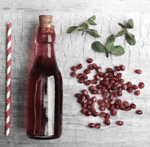 Fresh cocktail preparation: soda bottle, pomegranate, straw on grey table background, top view
