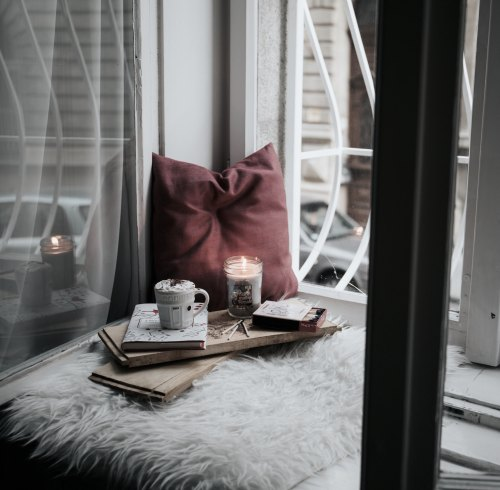 book with hot chocolate by the window