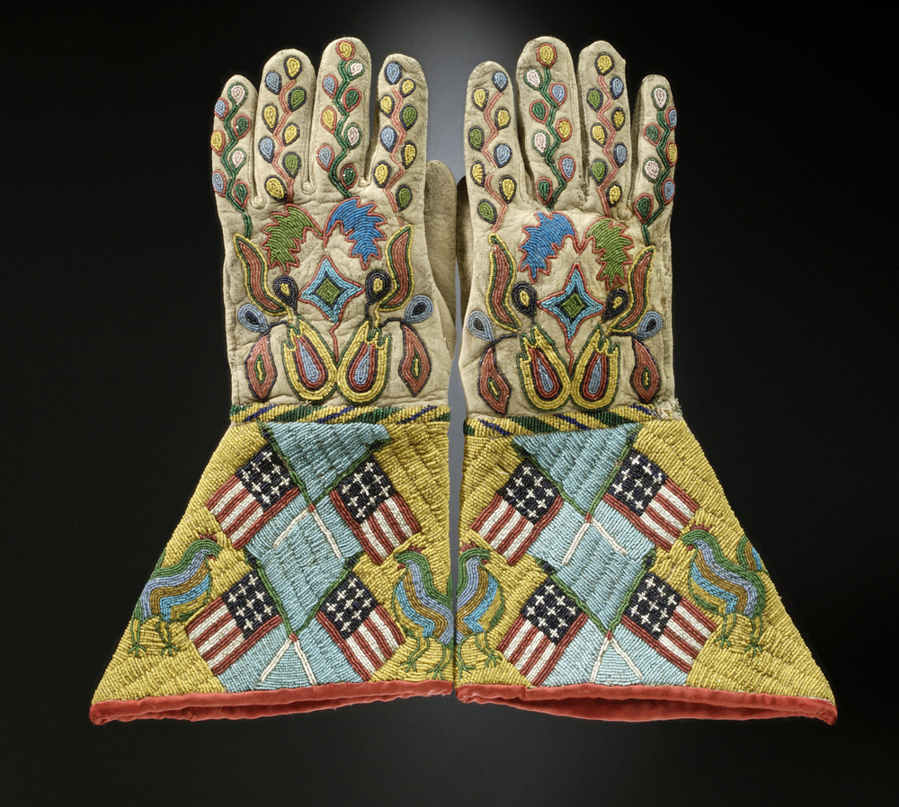 Gauntlets, c. 1890. Sioux-Métis artist, North or South Dakota. Native tanned leather, glass and brass beads, cotton cloth. 14 ó x 8 in. (36.8 x 20.3 cm) United States, Hirschfield Family Collection, Courtesy of Berte and Alan Hirschfield.