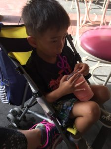 Tyler enjoying smoothie in umbrella stroller