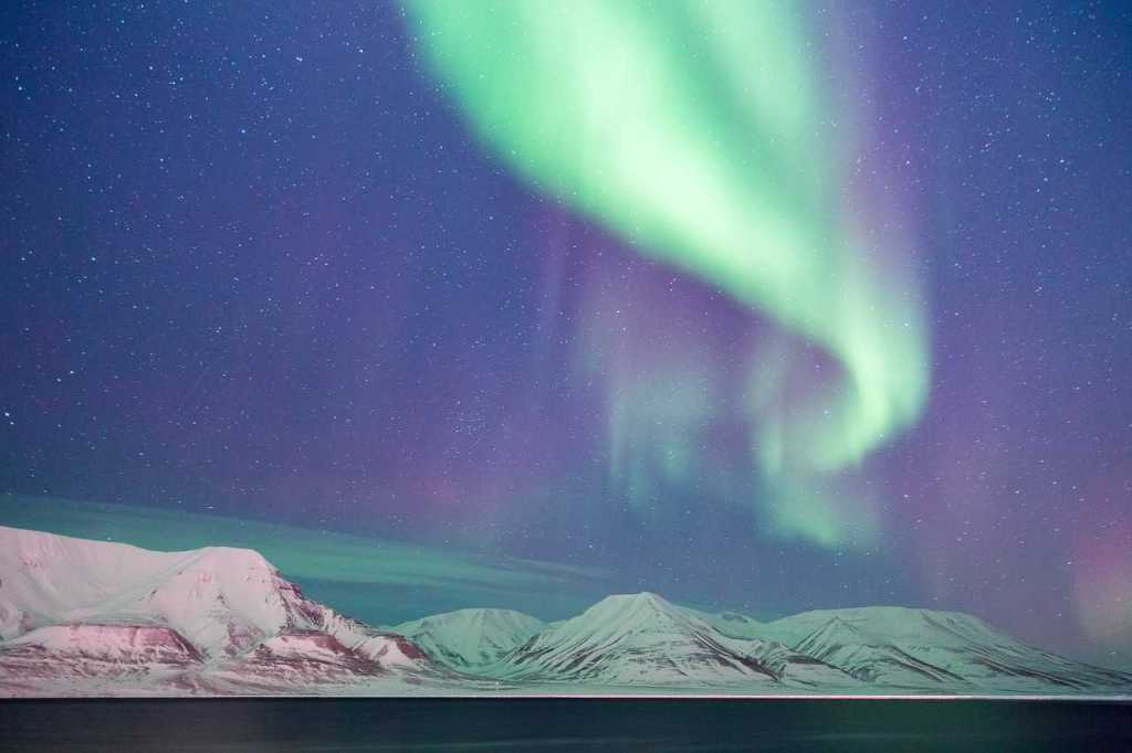 View of the Northern Lights in the sky above white mountains in Svalbard