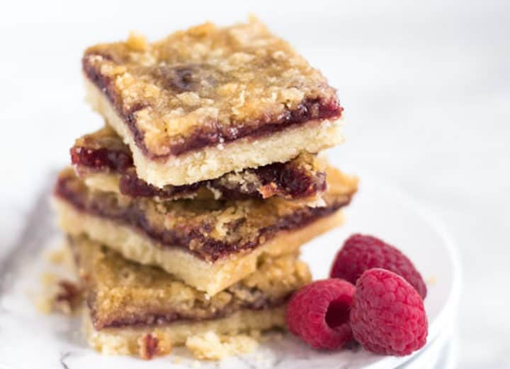 raspberry crisp bars stacked up with 3 fresh raspberries