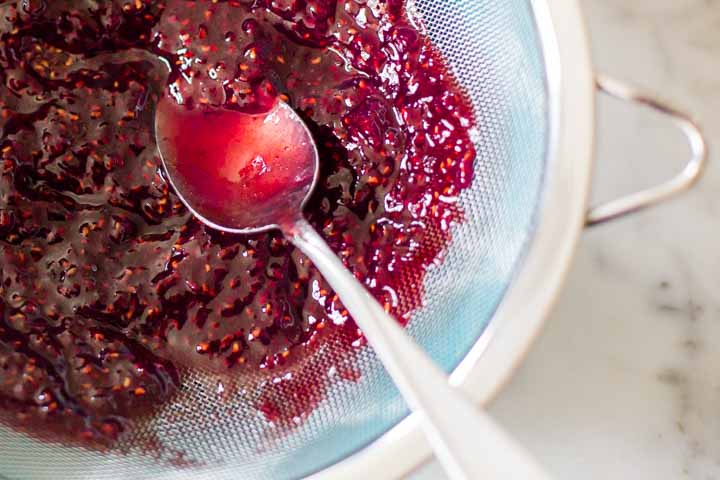 raspberry preserves in a strainer over a bowl