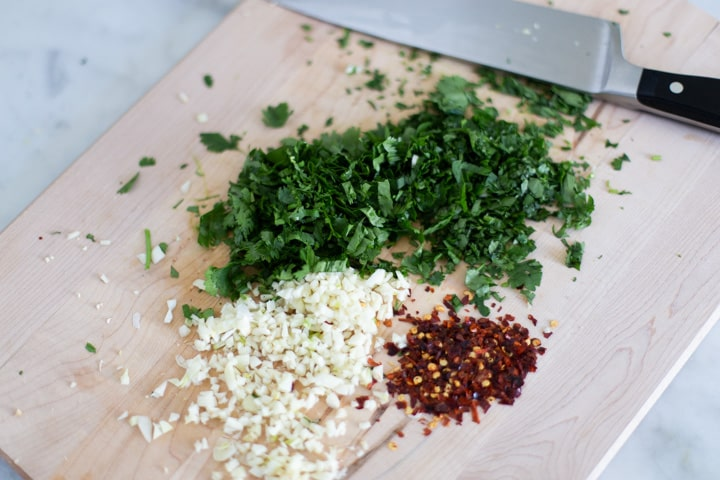 chopped cilantro, garlic, and crushed red pepper on a cutting board