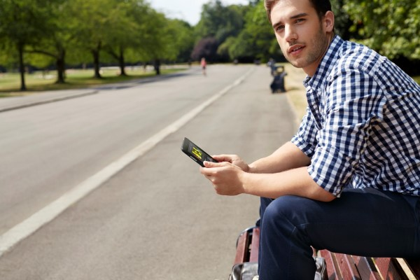 Young Man Using Venue 7 Tablet Outside