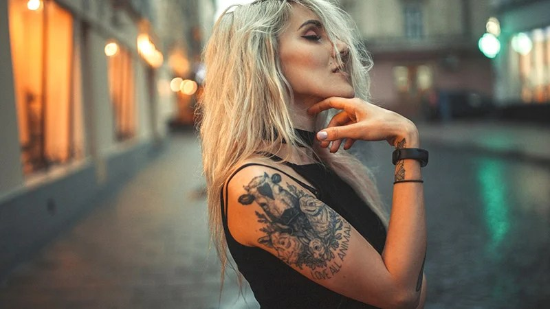 Young Woman Portrait With Tattoo On Shoulder Standing On City St