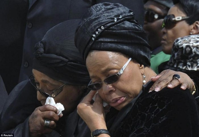 Winnie Mandela (left), ex-wife of former South African President, and Graca Macel, widow of Mandela, wipe away tears as his flag-draped coffin arrives at the Mthata airport