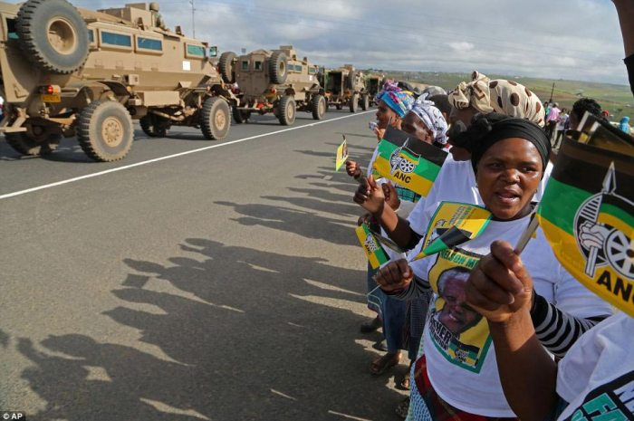 Women hold ANC flags and banners as the long convoy bringing Mandela's body home finally arrives in Qunu