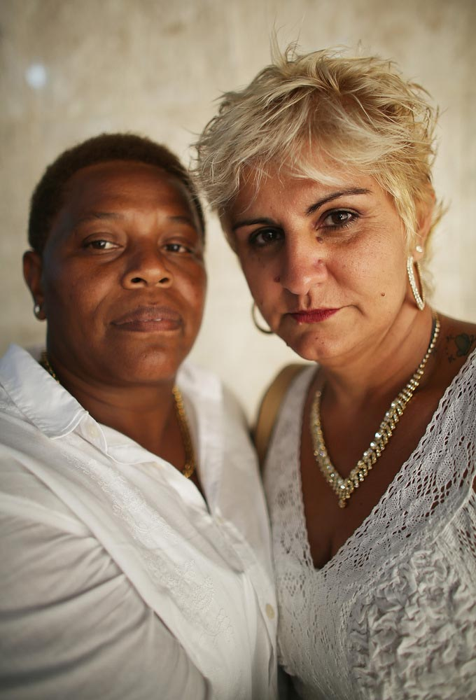 RIO DE JANEIRO, BRAZIL - DECEMBER 08: Newly married couple Nelzete (L) and Danisa, together for three years, pose at what was billed as the world's largest communal gay wedding on December 8, 2013 in Rio de Janeiro, Brazil. 130 couples were married at the event which was held at the Court of Justice in downtown Rio. In May, Brazil became the third country in Latin America to effectively approve same-sex marriage via a court ruling, but a final law has yet to be passed. (Photo by Mario Tama/Getty Images)