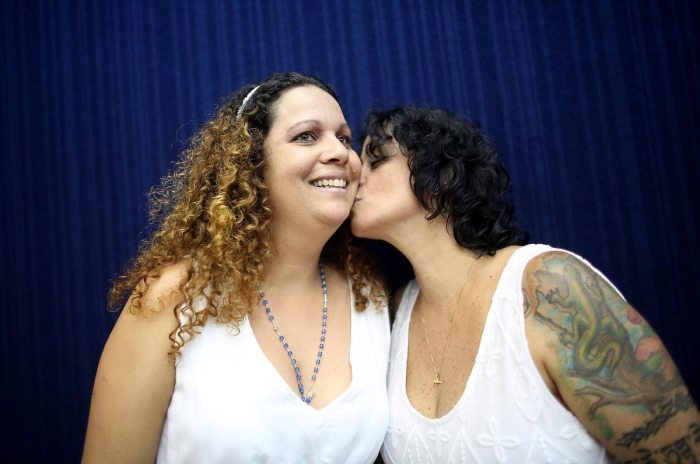 Couple Roberta Felitte and Karina Soares, together five years, kiss while posing before marrying at what was billed as the world's largest communal gay wedding on December 8, 2013 in Rio de Janeiro, Brazil. 130 couples were married at the event which was held at the Court of Justice in downtown Rio. In May, Brazil became the third country in Latin America to effectively approve same-sex marriage via a court ruling, but a final law has yet to be passed. (Photo by Mario Tama/Getty Images)