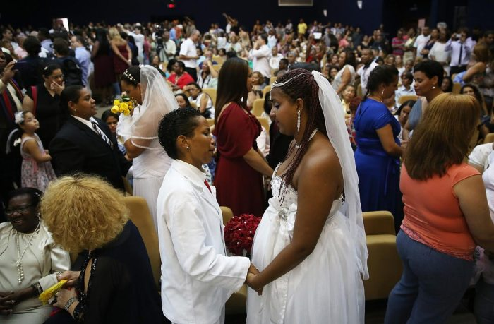 Joyce and Gabrieli (R) hold hands at what was billed as the world's largest communal gay wedding on December 8, 2013 in Rio de Janeiro, Brazil. 130 couples were married at the event which was held at the Court of Justice in downtown Rio. In May, Brazil became the third country in Latin America to effectively approve same-sex marriage via a court ruling, but a final law has yet to be passed. (Photo by Mario Tama/Getty Images)